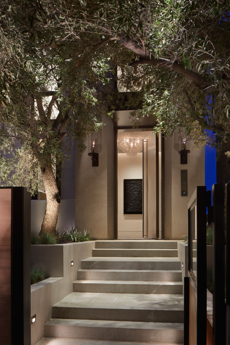 The tree and steps leading to this modern front door are highlighted at night by built-in lighting. #Landscaping #ExteriorStairs