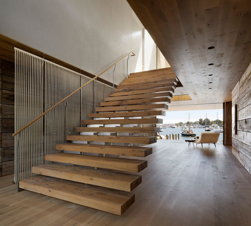 Wide wood stairs connect the ground level with the upper floor of this modern house, while adjacent to the stairs is a see-through screen made from rope that draws inspiration from local crafts and traditional materials. #WoodStairs #ModernStairs