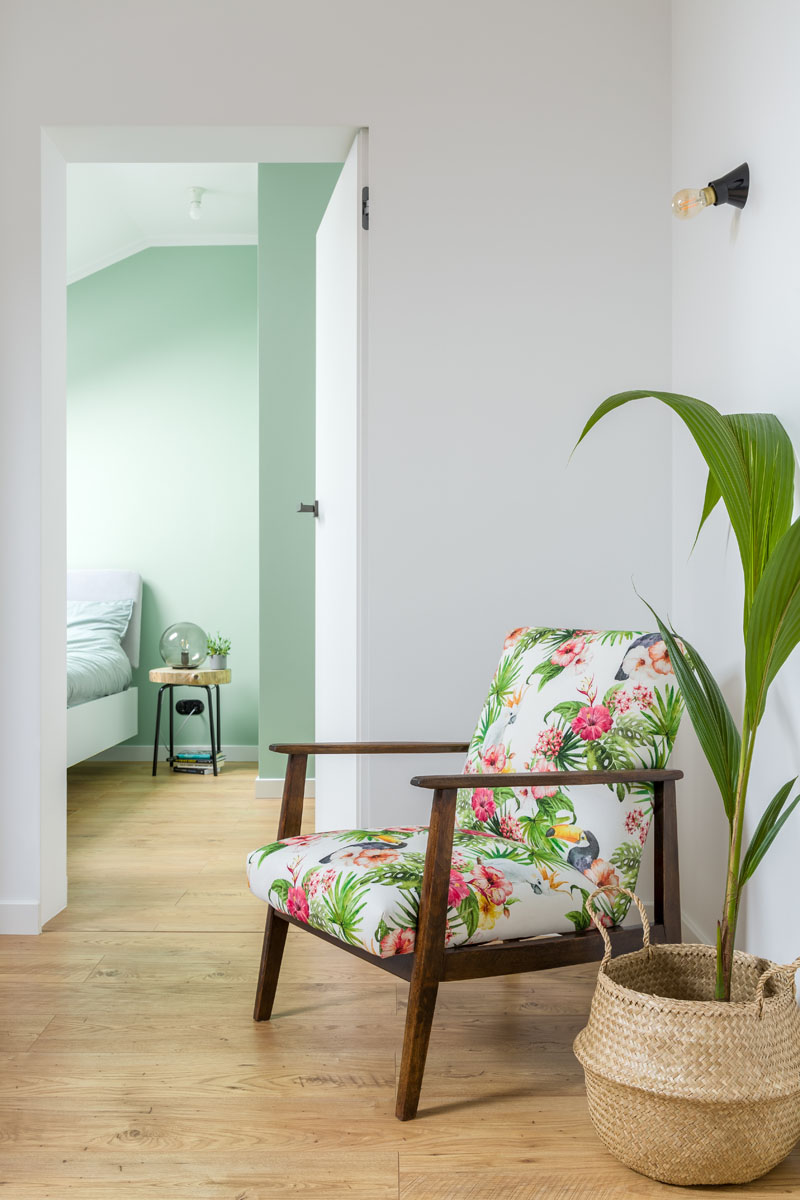A white door that blends into the wall by the floral armchair at the top of the stairs, provides access to the bedroom in this modern apartment. #InteriorDesign #MintGreen #Interiors #Apartment