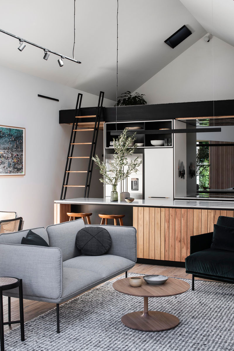 A ladder, that normally hangs on the wall, can be used to gain access to the loft above the kitchen in this modern interior. #Loft #Ladder #ModernInterior
