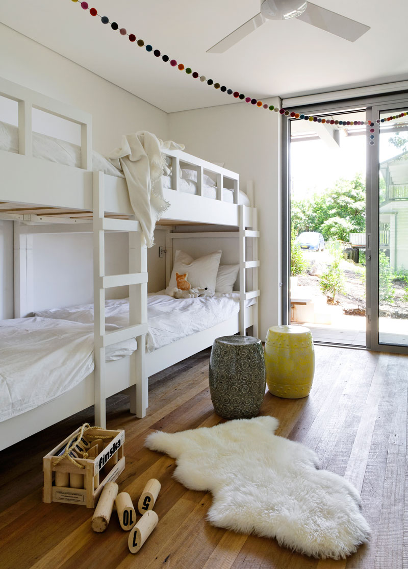 In this kids bedroom, bunk beds have been included to create enough room for four to sleep, and a sliding glass door opens to the garden. #KidsBedroom #BunkBeds