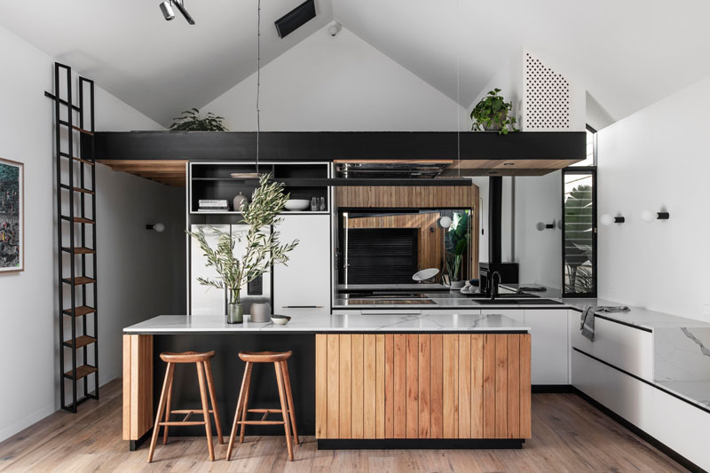 In this modern kitchen, a large island with black accents complements the black edge of the loft, while a mirrored backsplash reflects the backyard. #ModernKitchen #KitchenDesign #BlackAccents