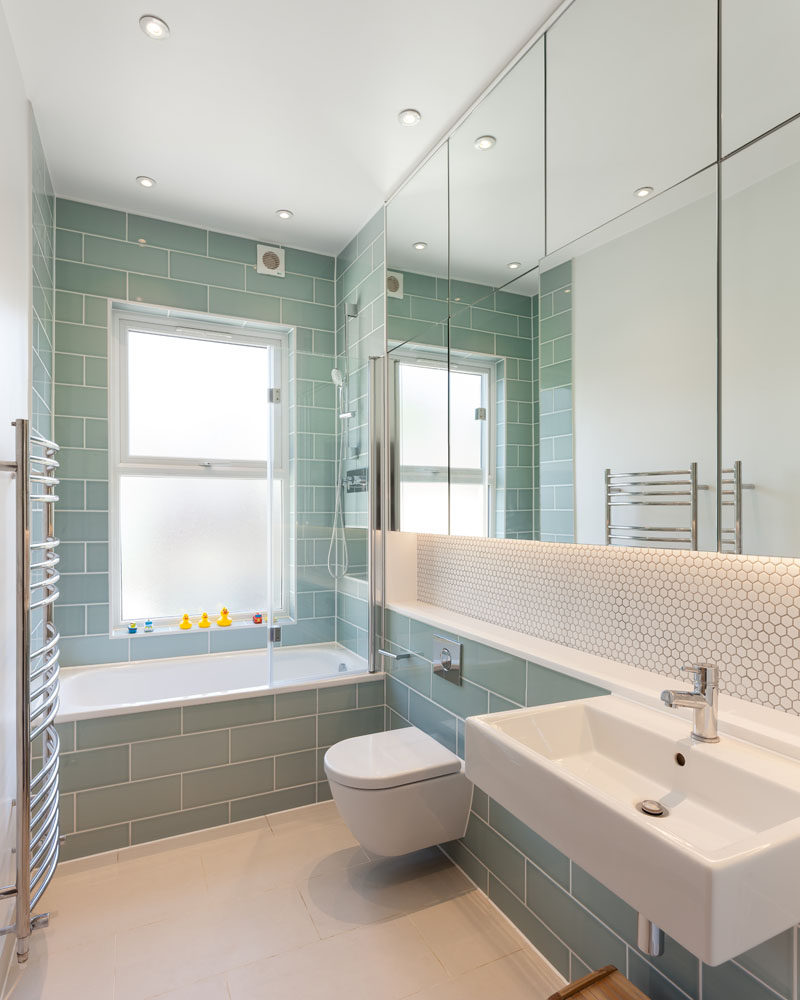 In this modern bathroom, light green subway tiles have been paired with white penny tiles and a large group of mirrors. #GreenTiles #ModernBathroom #BathroomDesign