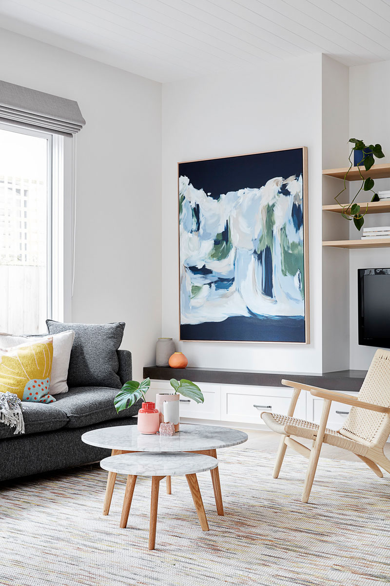 In this modern open plan living room, custom cabinetry lines the wall underneath the television, while abstract wall art and cushions add a touch of color. #LivingRoom #InteriorDesign #LivingRoomIdeas