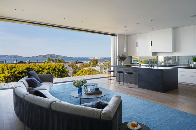 Sliding doors open the interior of this modern house to the balcony where uninterrupted water views can be enjoyed. #Balcony #Kitchen #LivingRoom