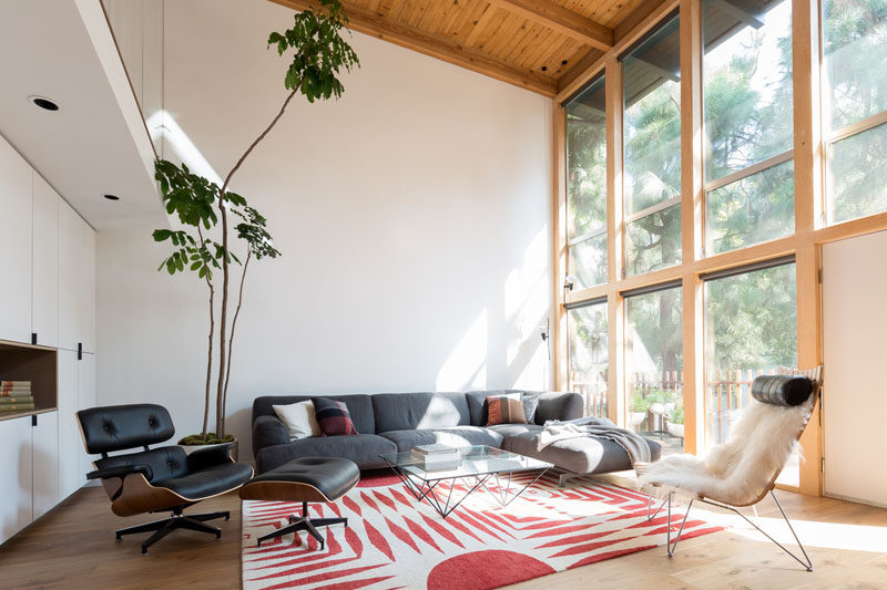 Large double-height, wood framed windows flood the updated interior with natural light. The bright interior strongly contrasts the dark exterior of the house. #LivingRoom #MidCenturyModern #Windows