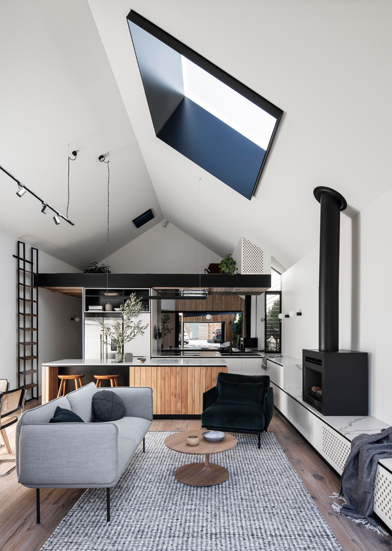 In this modern interior, the vaulted ceiling creates a tall and open space for the new living room, dining room, kitchen, and loft area. In the living room, the couch is focused on the black fireplace, that sits on a custom built low shelf. #ModernInterior #LivingRoom #Skylight #VaultedCeiling #BlackFireplace