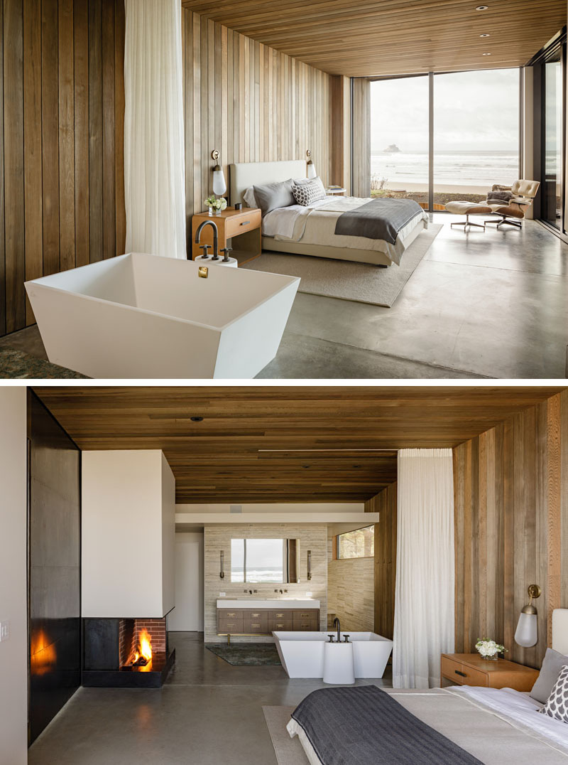 In this modern master bedroom, wood walls has been installed to match the wood ceiling, while the ensuite bathroom has been left open, allowing for water views from the bathtub. #MasterBedroom #WoodWalls #WoodCeiling #OpenBathroom #Fireplace