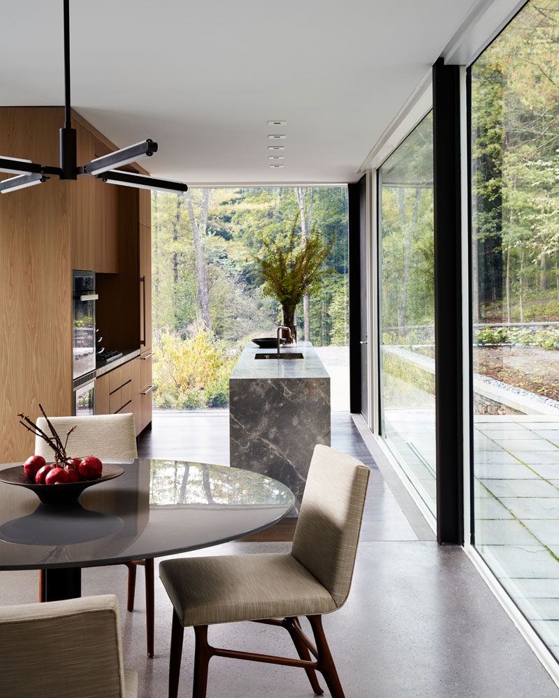 In this modern kitchen, wood cabinets have been combined with a grey countertop for a contemporary look, while floor-to-ceiling glass walls fill the room with natural light. #Kitchen #Windows #GlassWalls