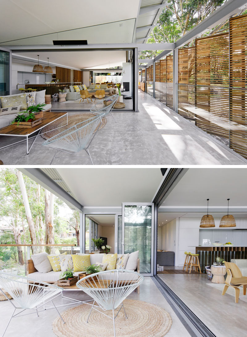 Folding glass doors open the living room in this modern house to a secondary outdoor living room, that's furnished with another couch and has views of the trees. #OutdoorLivingRoom #ModernInterior #GlassDoors