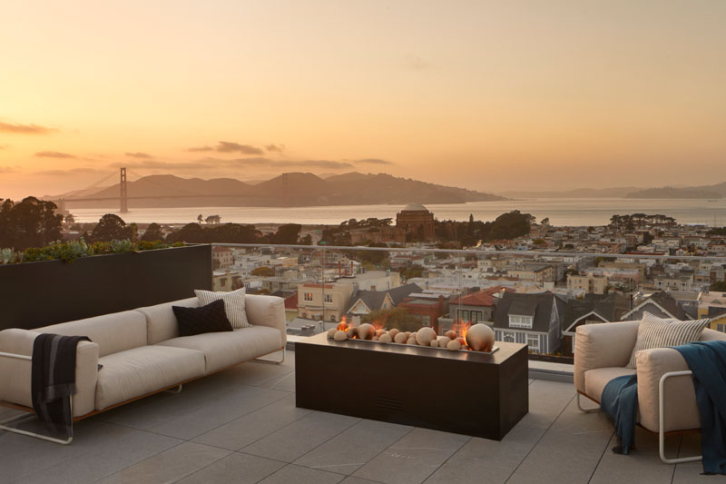 This modern house has a rooftop deck that features a lounge with a freestanding fire pit, and views of the city and Golden Gate Bridge. #RooftopDeck #OutdoorLounge