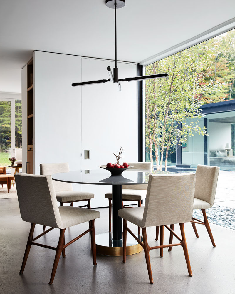 In this modern dining room, a round dining table with a glossy top reflects the light, while a four-armed pendant light hangs above. #ModernDiningRoom #InteriorDesign