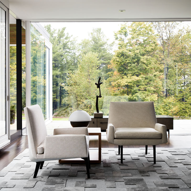 This modern sitting area has a textured grey rug, while floor-to-ceiling glass walls provide uninterrupted views of the trees outside. #SittingRoom #LivingRoom #InteriorDesign