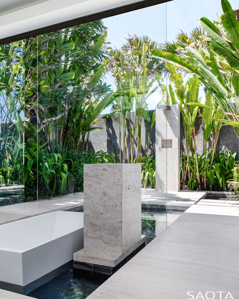 In this modern master ensuite bathrooms, a sunken bathtub is surrounded by a water feature that flows to the outdoors, where an outdoor shower is surrounded by lush landscaping. #SunkenBathtub #OutdoorShower #ModernBathroom