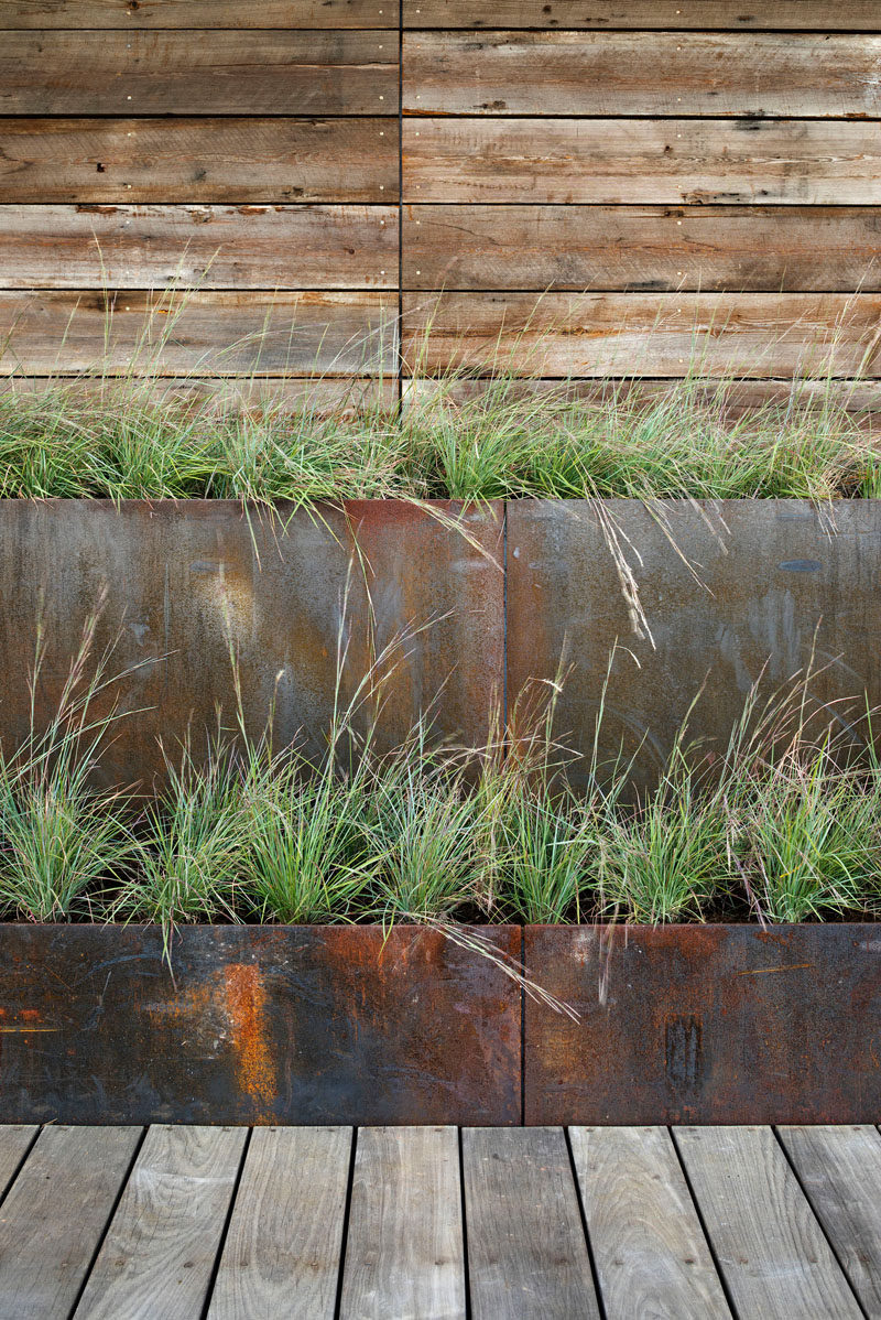 This modern house uses stepped weathering steel planters to mediate between the boardwalk level and the ground level, which is elevated above the floodplain. #SteelPlanters #ModernPlanters.