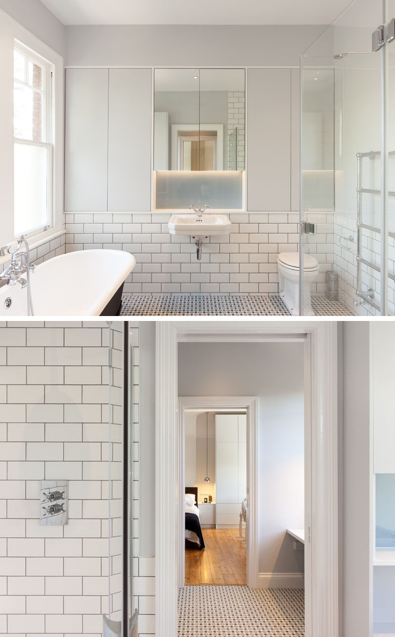 In this contemporary bathroom, white subway tiles with dark grout cover the walls, while a freestanding bathtub with a black exterior creates contrast. #ContemporaryBathroom #WhiteSubwayTiles