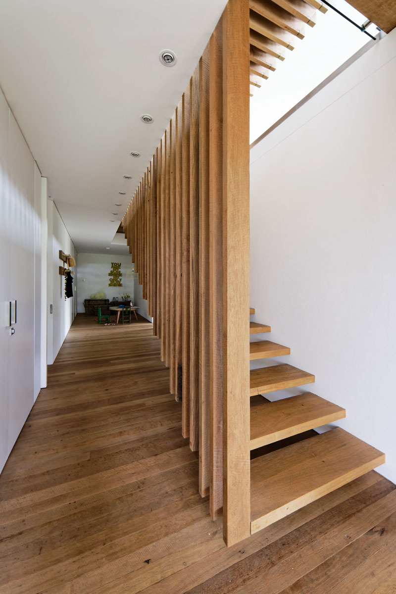 This modern house features suspended wood stairs that connect the living areas with the bedrooms below. #SuspendedStairs #WoodStairs #ModernStairs