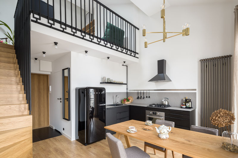 Oak stairs runs alongside the wall of this modern apartment, and leads up to the mezzanine that features a custom-designed black steel balustrade that was designed to add character to the interior. #ModernApartment #InteriorDesign #Balustrade #Stairs