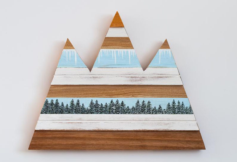 Made with collected scrap wood of all kinds, this mountain artwork shows painted trees and horizontal stripes representing the sky and snow. #MountainWallArt #MountainArt #MountainDecor