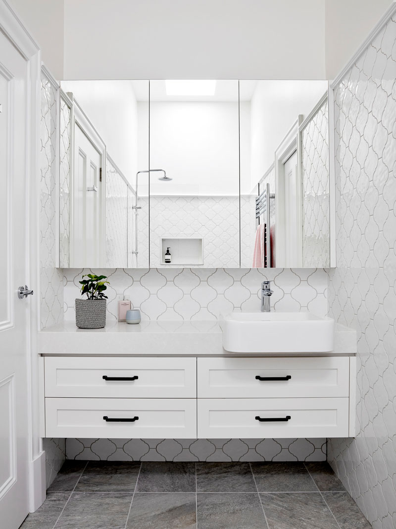 In this contemporary bathroom, an arabesque tile pattern in white covers the walls, while the wall-to-wall mirror reflects the shower and the natural light from the skylight. #WhiteBathroomIdeas #ContemporaryBathroom #TileIdeas