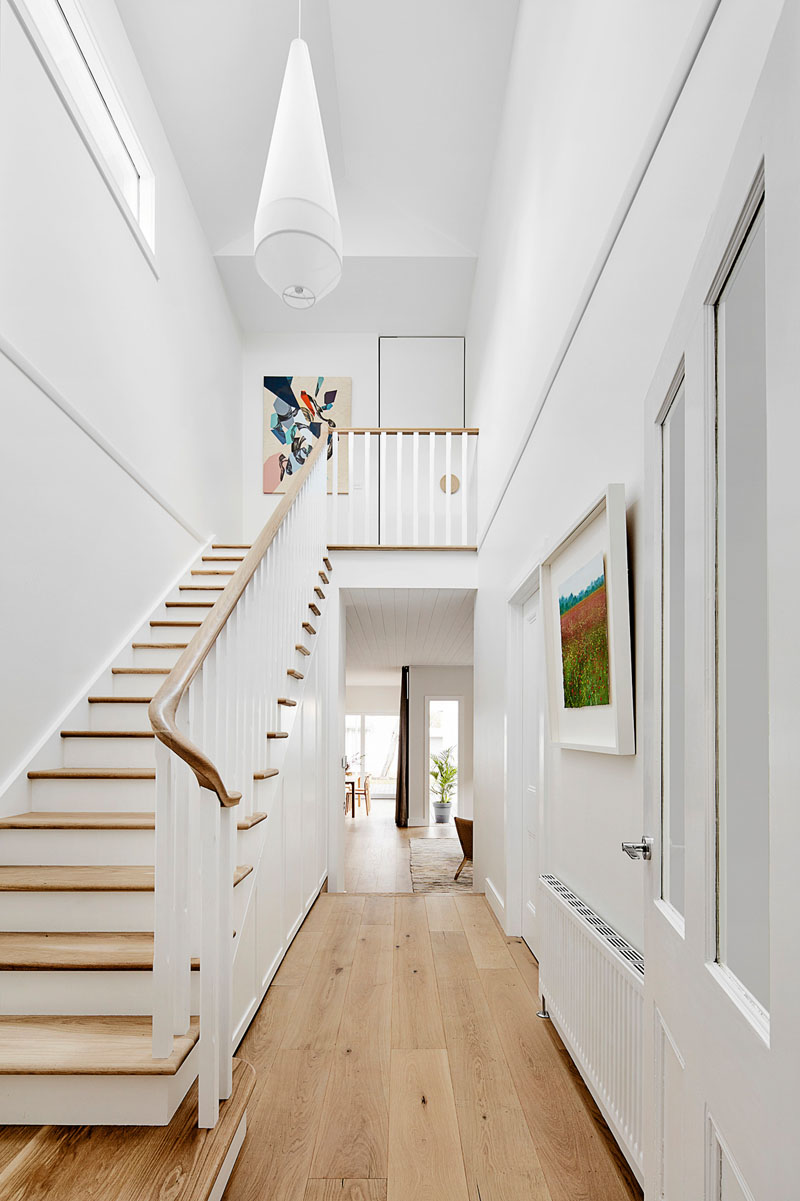 A central double height space containing the stair separates the new addition from the original home, and allows light to flow throughout the space. #Staircase #DoubleHeightEntryway