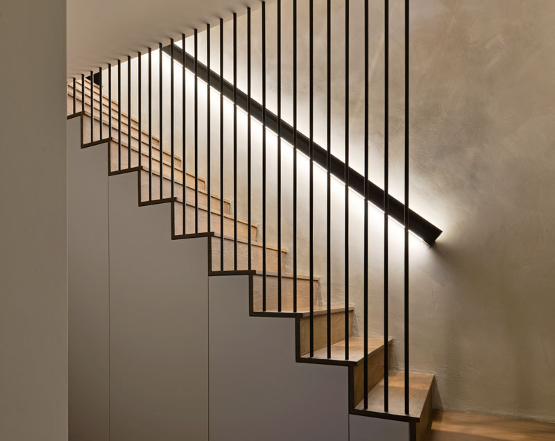 These modern wood stairs have a handrail with hidden lighting, and a floor-to-ceiling steel rod safety barrier. #WoodStairs #Handrail #BacklitHandrail