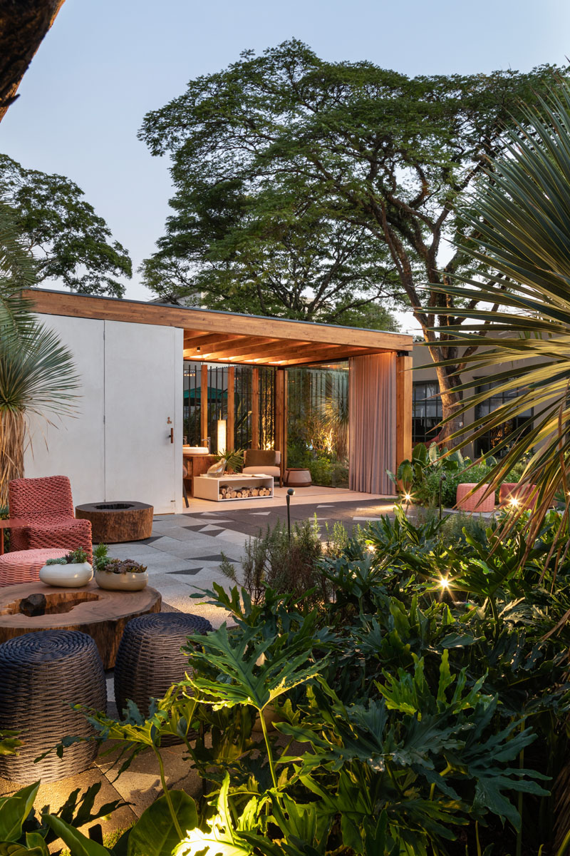 This modern outdoor terrace includes a wooden structure made from Brazilian pinus, wall coverings and flooring made of concrete, a toilet area, waiting lounge, and a counter with basins and a fireplace. #OutdoorTerrace #Terrace #Architecture #OutdoorSpace