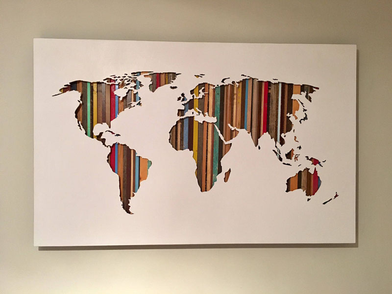 This modern world map has a colorful background that's created using reclaimed wood, that help to bring the silhouette to life.