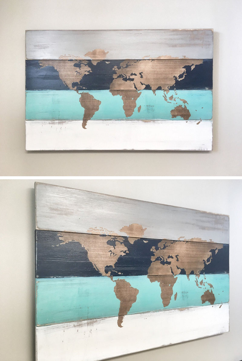 This wall art has a world map with a natural wood texture, that's surrounded by painted grey, navy, aqua, and white horizontal elements.