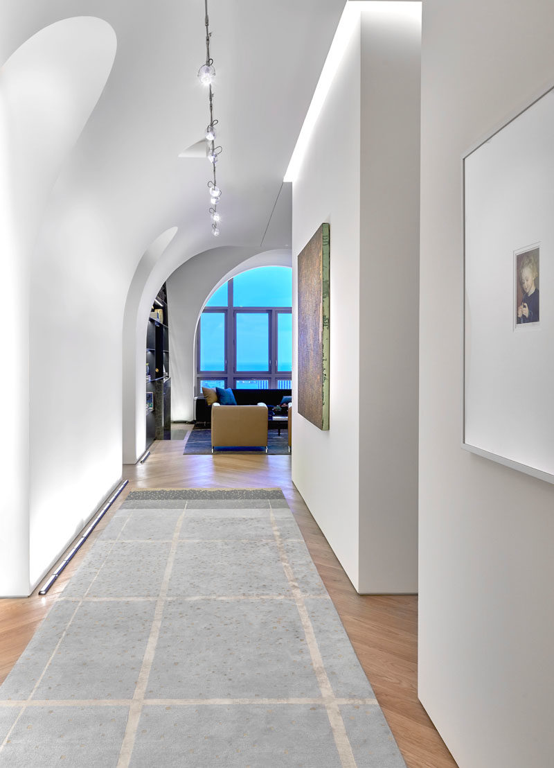 Arches in this modern penthouse offer dramatic space for the owner's art collection and temper the impact of 14-foot ceilings.  #Arches #Architecture #Hallway #VaultedCeiling #HighCeilings
