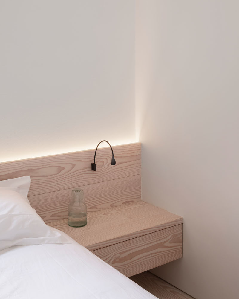 Bedroom Ideas - This simply finished modern bedroom features flush faced built-in hanging cupboards, bespoke Douglas fir bedside cabinetry, and hidden lighting that creates a calm atmosphere. #bedroomIdeas #WoodHeadboard #ModernBedroom #HiddenLighting
