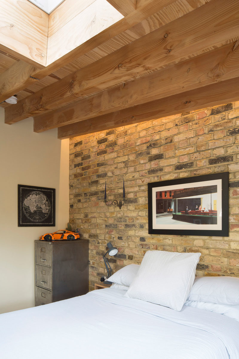Bedroom Ideas - In this bedroom, a brick wall provides a backdrop for the bed, while wood beams have been left exposed, and a skylight adds natural light. #BedroomIdeas
