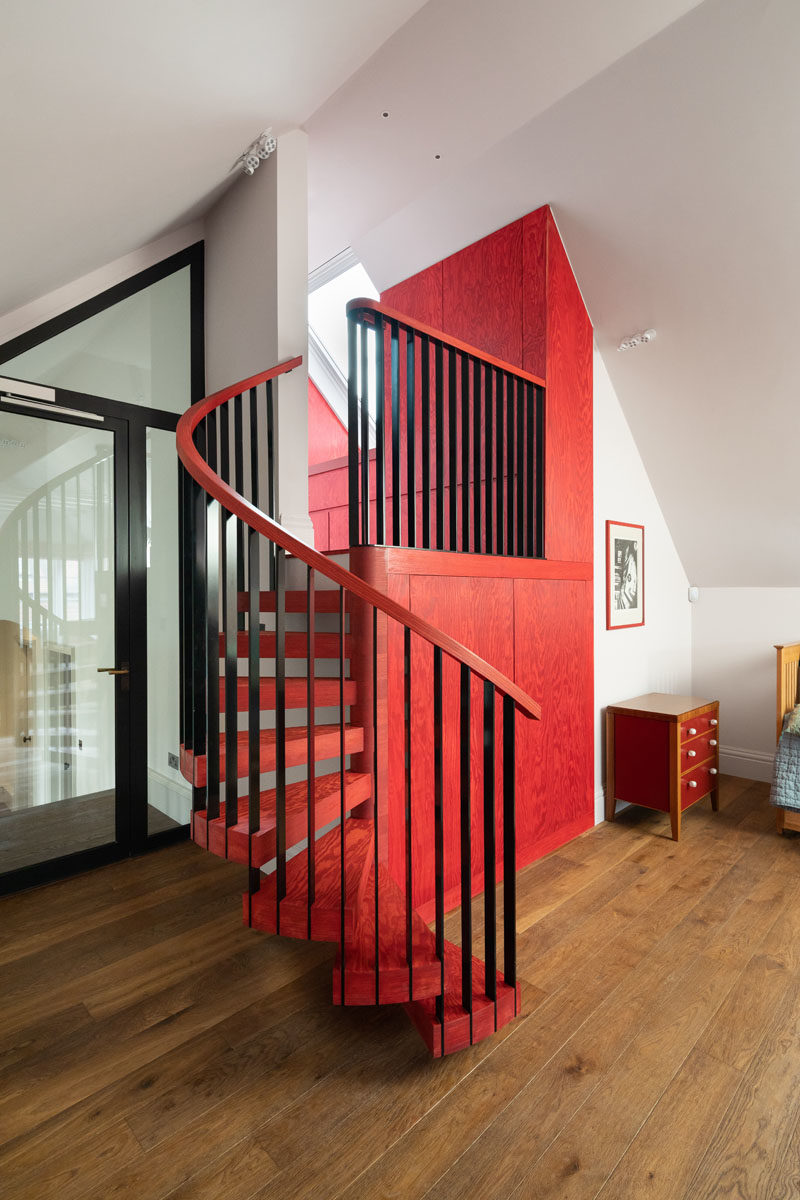 Stair Ideas - Red Linseed oiled Douglas Fir and custom ironmongery has been used to create built-in storage and spiral stairs that lead up to a matching bathroom. #SpiralStairs #RedCabinets #StairIdeas