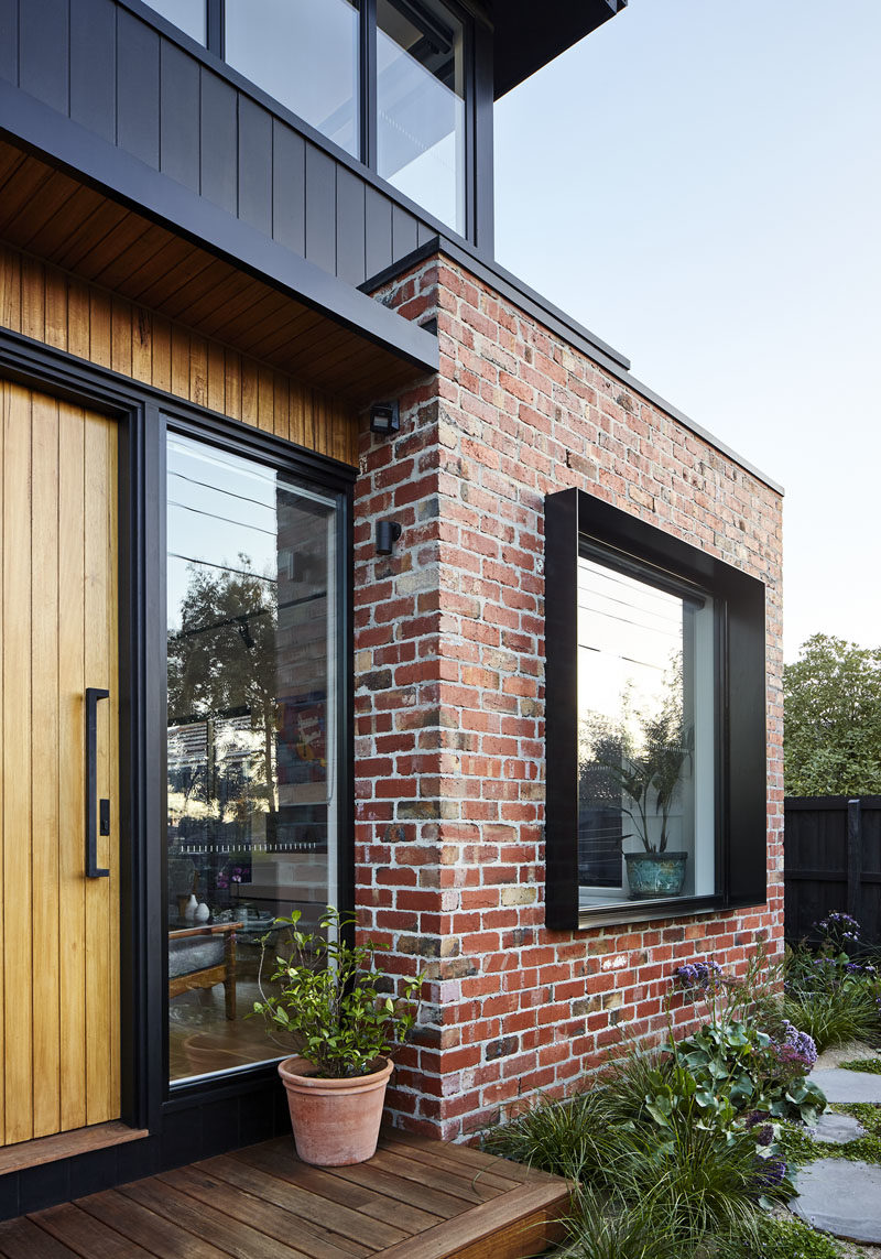 Surrounded by the recycled bricks is a deep steel window box detail that adds depth and shadow to this modern house facade. #Window #Bricks #ModernHouse