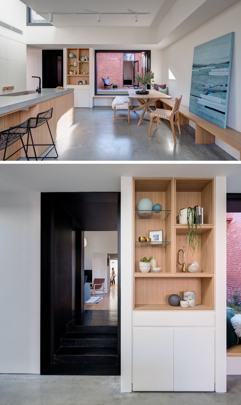 In this modern home interior, the dark hallway opens up to the new addition that houses the main social areas. A built-in wood shelf is surrounded by white walls and cabinetry, a strong contrast to the black hallway. #ShelvingIdeas #WoodShelving #OpenPlanLiving