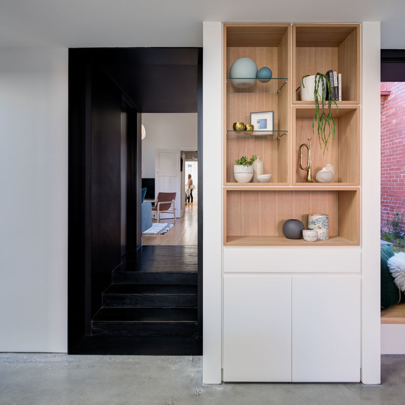 Shelving Ideas - In this modern home interior, the dark hallway opens up to the new addition that houses the main social areas. A built-in wood shelf is surrounded by white walls and cabinetry, a strong contrast to the black hallway. #ShelvingIdeas #WoodShelving #OpenPlanLiving