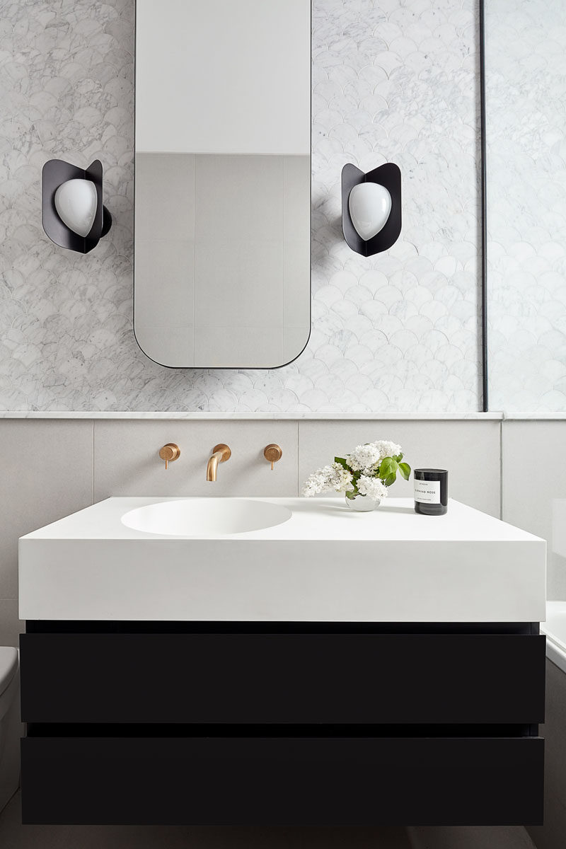Bathroom Ideas - In this modern bathroom, a rounded rectangular mirror hangs above a small black and white vanity, while the black sconces complement the lower section of the vanity. #BathroomIdeas #ModernBathroom