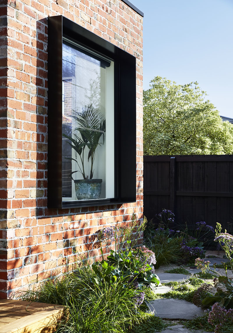A protruding black frame highlights this window on a modern house that also features recycled brick. #BlackWindowFrame #RecycledBrick #ModernHouse