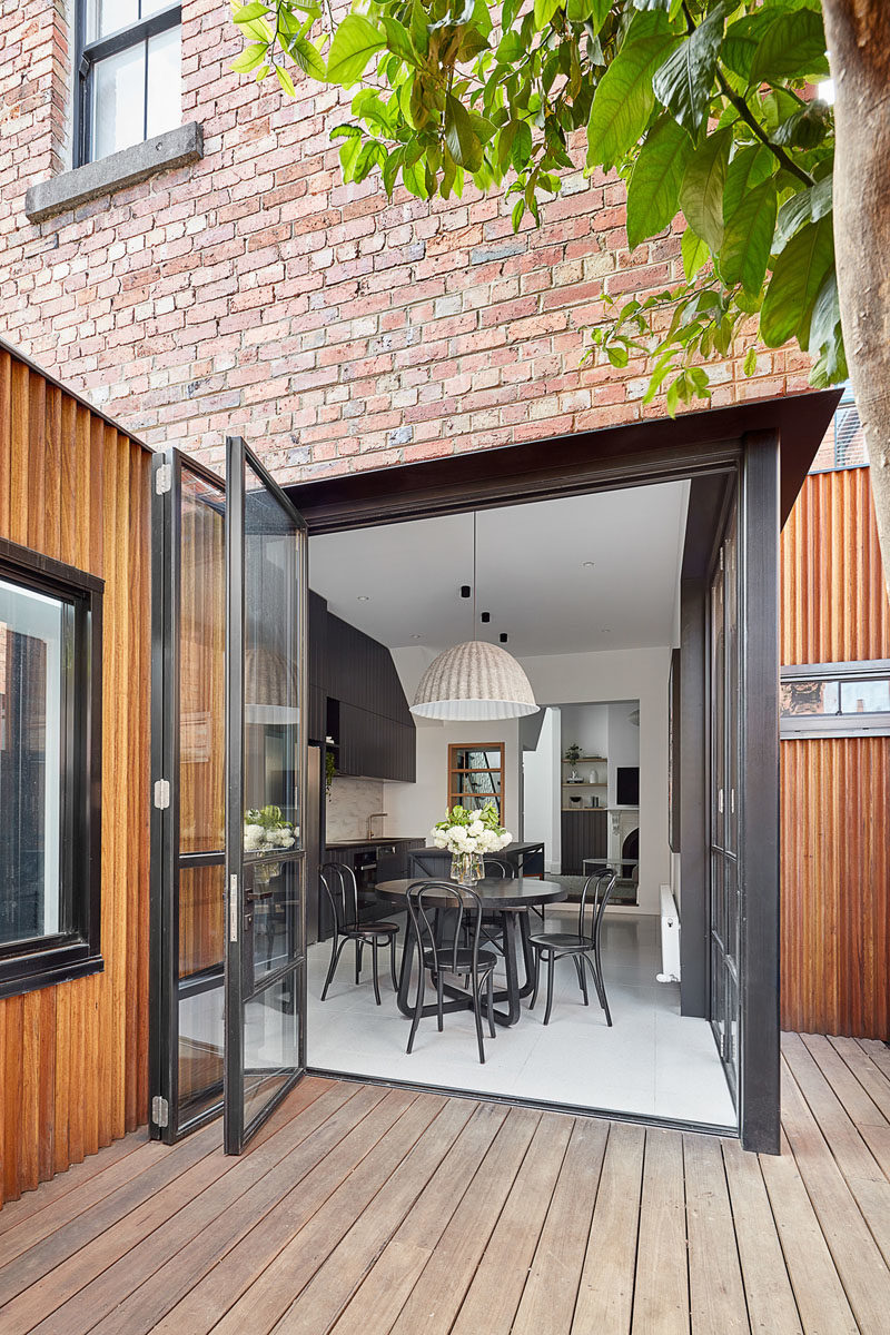 This modern house has folding black-framed glass doors that open the black kitchen and dining area to a small courtyard. #BlackDiningRoom #BlackKitchen #FoldingDoors #GlassDoors