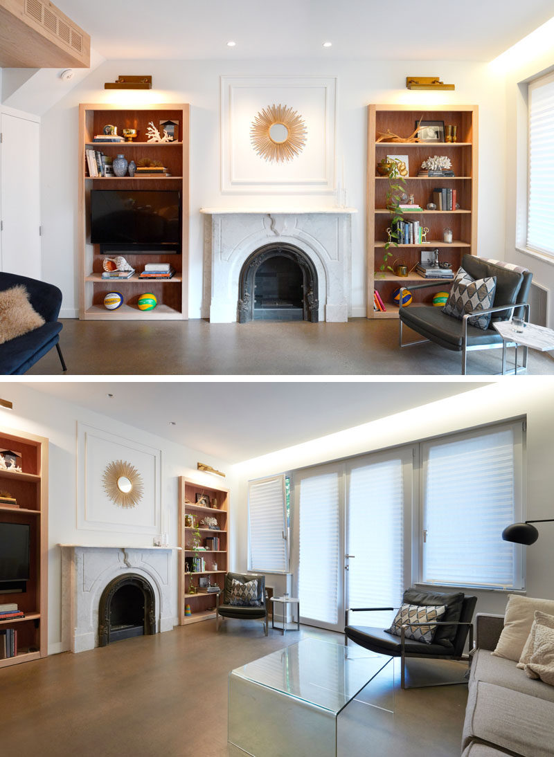 Bookshelf Design Ideas - Wood-lined, built-in bookshelves have been added to either side of the fireplace. Sconces highlight the top shelves, while blank space has been left above the fireplace for artwork. #LivingRoom #BookshelfDesignIdeas #Fireplace