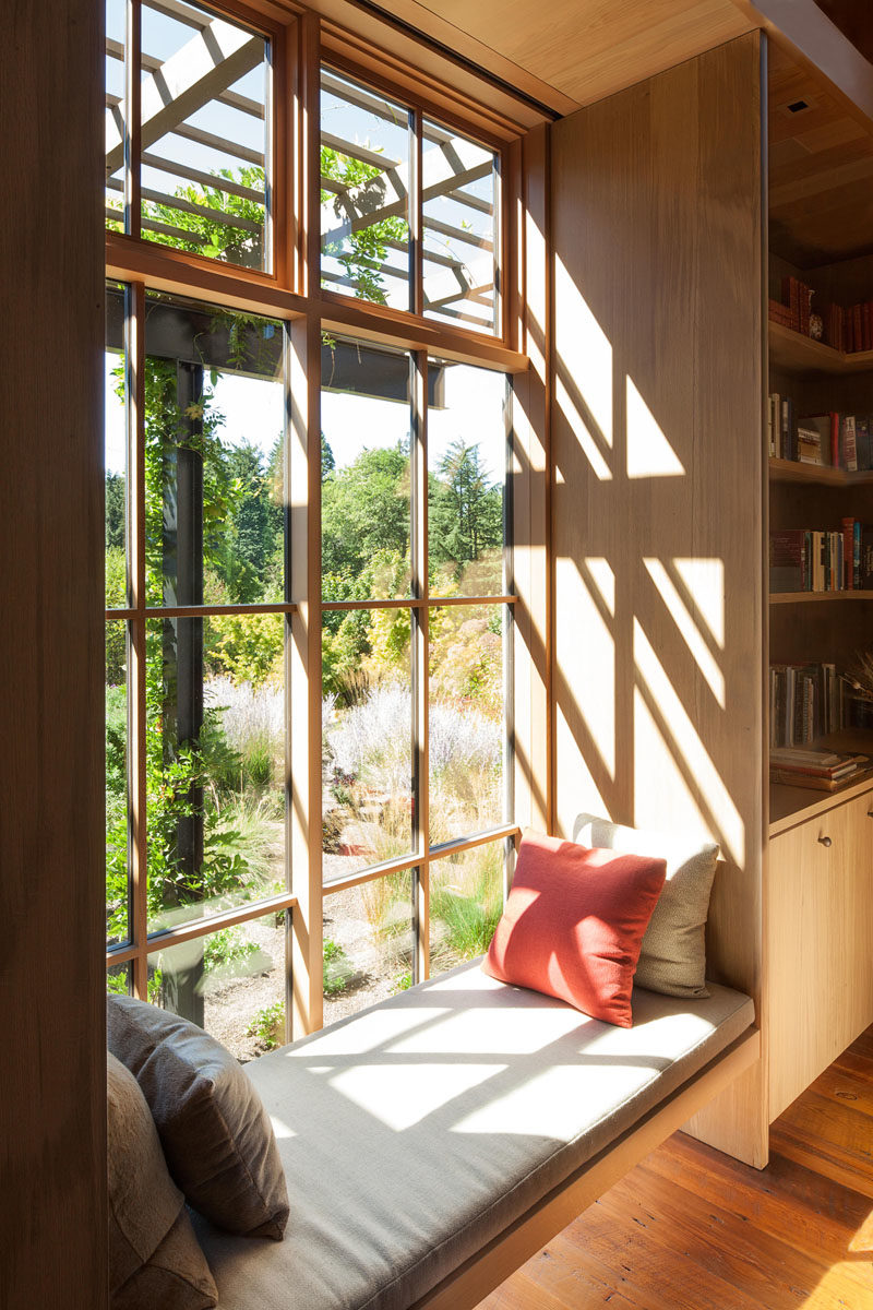 Window Seat Ideas - In this den, built-in bookshelves line the walls, while a window seat provides a place to quietly read and enjoy the views outside. #WindowSeat #Seating #Den #Bookshelves