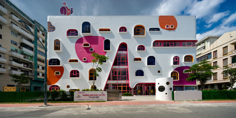 Facade Ideas - The white facade of the kindergarten features pops of color that complement the colorful geometrically shaped window frames. #FacadeIdeas #Architecture #UniqueWindowShapes