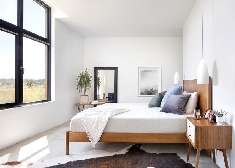 Bedroom Ideas - In this modern bedroom, wood furnishings and a plan help to bring nature indoors, while the black framed windows allow an abundance of natural light to fill the room. #BedroomIdeas #BedroomDesign #ModernBedroom