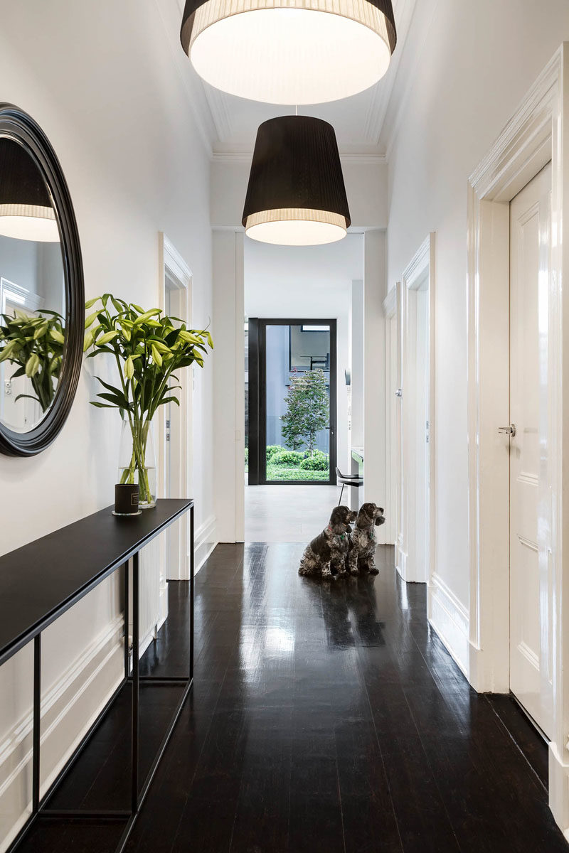 Hallway Ideas - Sight lines were introduced to capture the views of the pool and garden from the key areas of the home, like in the hallway that's brightened with the use of two pendant lamps. #Hallway #InteriorDesign #HallwayIdeas