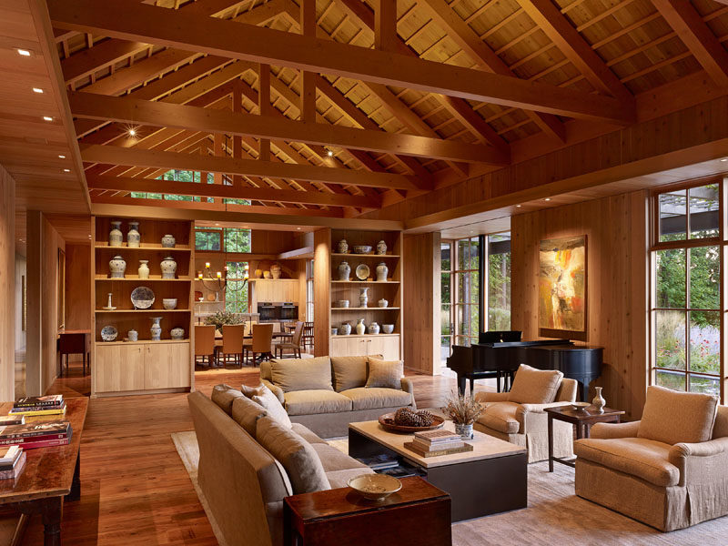 Living Room Ideas - Built-in shelves and cabinets show off a collection of porcelain, while the exposed wood ceiling draws the eye upwards, and the windows fill the room with natural light. #LivingRoom #ExposedCeiling #CustomCasework #Windows
