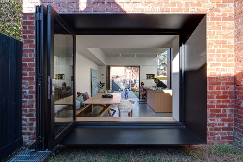 Window Ideas - A large window with a deep steel frame opens up to a small grassy courtyard. #WindowIdeas #WindowDesign
