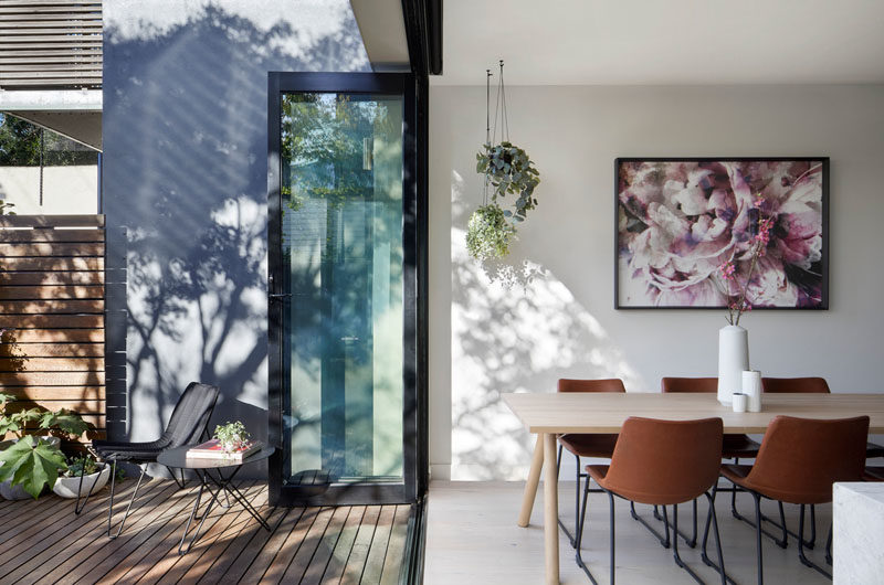 Dining Room Ideas - In this modern dining area, artwork hangs on the wall, while plants hang from the ceiling, and folding glass doors open to the deck and yard. #DiningRoomIdeas #FoldingDoors #DiningRoom