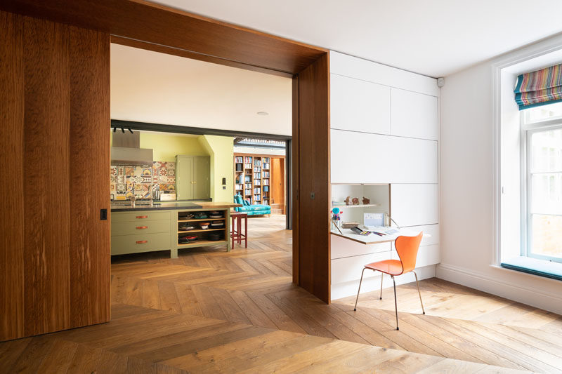 Wall Desk Ideas - This modern playroom has a window seat and twin hidden writing desks that fold-down from the wall. A large wood pocket door connects the playroom with the kitchen and dining area. #WallDesks #WindowSeat #LargeWoodDoor #PocketDoor