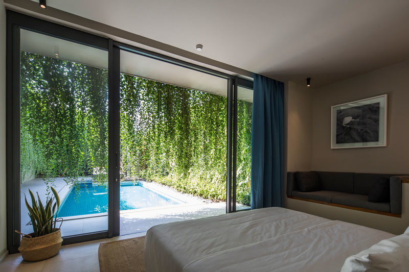 Bedroom Ideas - In this modern bedroom design, a built-in couch has been added along one wall, while hanging plants provide privacy. #HangingPlants #BuiltInCouch #BedroomDesign #BedroomIdeas