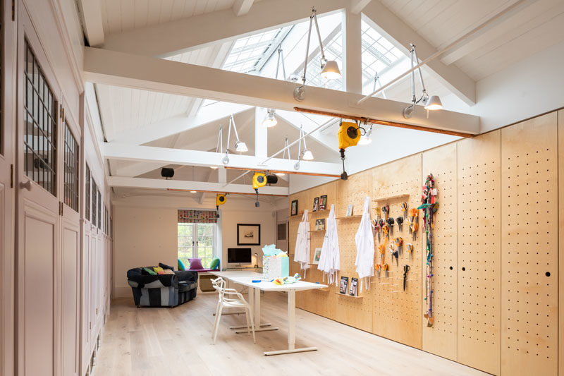 Home Studio Ideas - A large annex was converted into a studio space, to serve the client's small business, with skylights providing ample natural light, while a pegboard wall allows for custom shelving designs. #HomeStudio #HomeOffice #Workplace